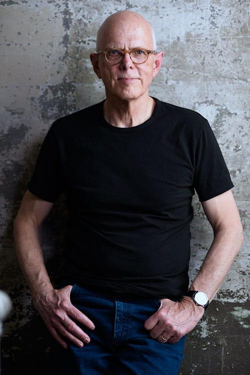Bruce Kramer in black t-shirt standing against grunge wall